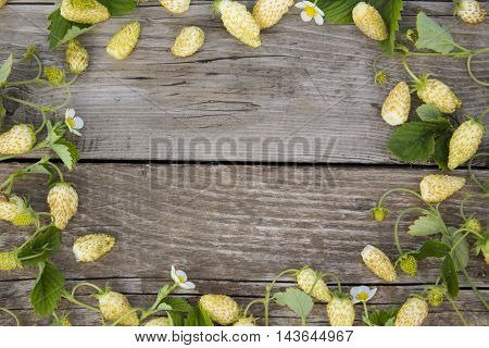 the bezels of the yellow strawberry, leaves and flowers on a background of old wooden planks