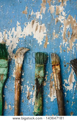 Old dried paint brushes on a wooden background