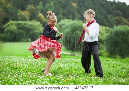 Childrens retro dance couple in suits, summer outdoors