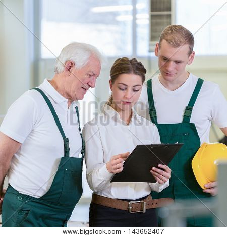 Young female director of warehouse and her two employees