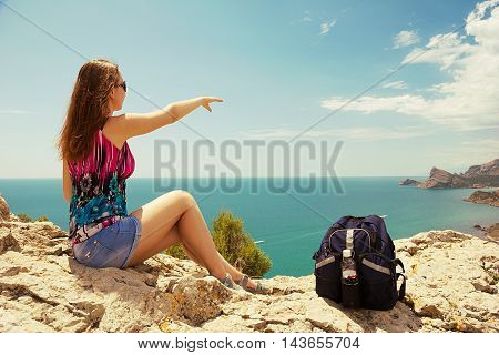 Woman traveler sits on the top of mountain and enjoys the beauty of seascape.