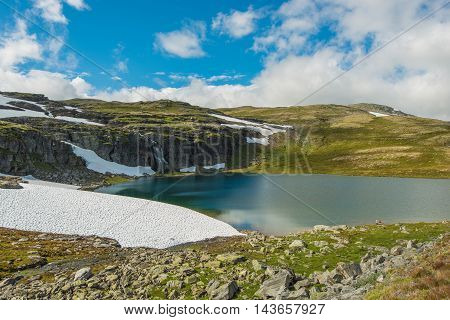 High Mountain Landscape. Norway Mountains Scenery with Lake Snow Spots and the Waterfall. Norway Geology.