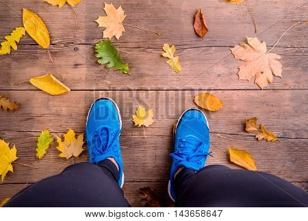 Legs Of Runner. Blue Sports Shoes. Colorful Autumn Leaves.