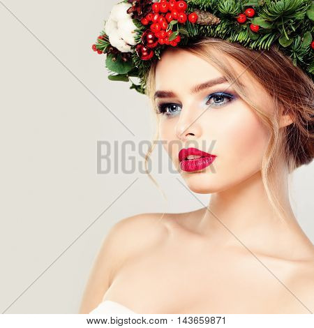 Beautiful Young Woman in Green Wreath on gray
