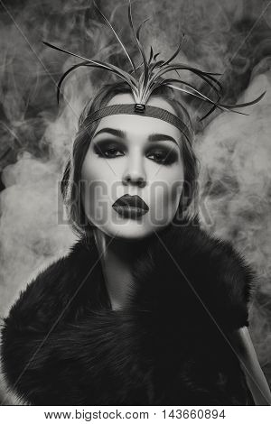 Beautiful young woman with smoky eyes and full red lips in fur. Vintage head piece. Studio beauty shot over smoky background. Copy space. Monochrome.