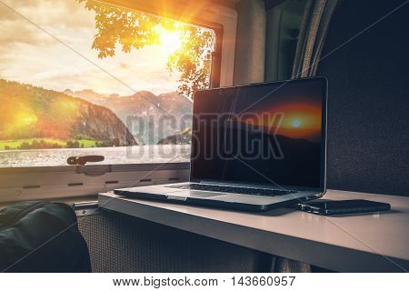 Working While Traveling. Laptop Computer on a Camper Table with Scenic Fjords View. Computer Working in the RV While Camping.