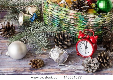 Wicker basket with Christmas ornaments, spruce branch, watches and cones on old wooden table.