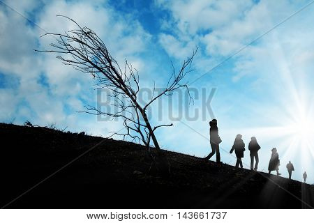silhouetted people walking over sunny sky