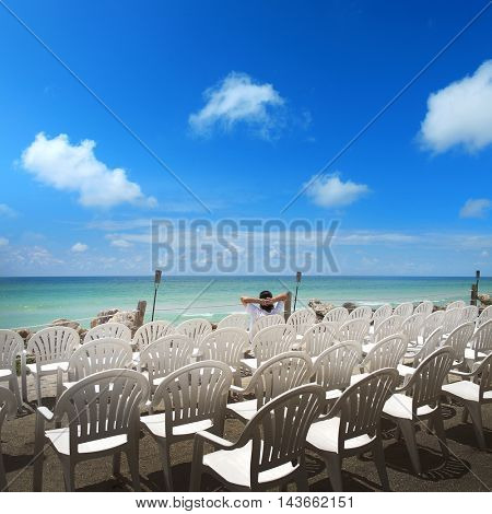 man sitting on chair at beach over clear sky