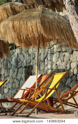 Orange and yellow sunbeds and straw sunshades in Italy