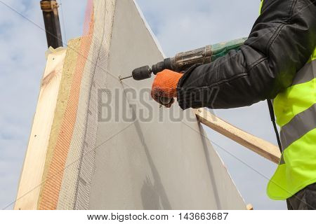 Roofer builder worker use drill to make a hole in structural Insulated Panel