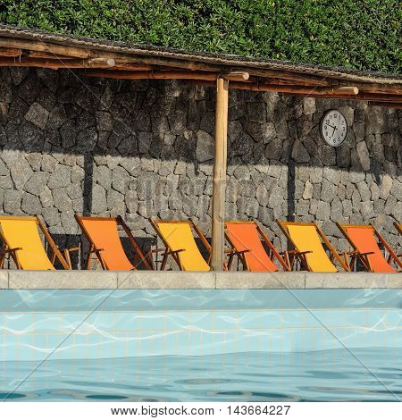 Mediterranean pool with orange and yellow sunbeds in Italy
