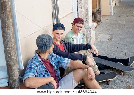 Positive teenage friends with skateboards sitting on pavement in summer day