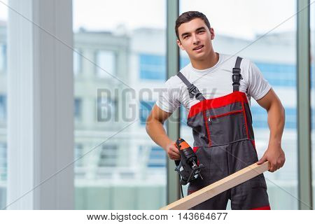 Young carpenter working at construction site