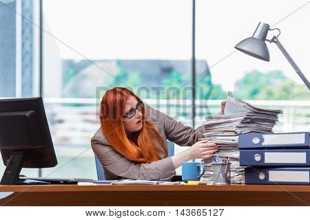 Stressed businesswoman with stack of papers