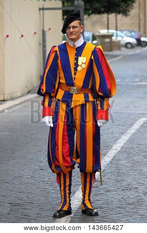 VATICAN CITY ITALY - APRIL 22: A Papal Swiss Guard stands guard at the entrance of Saint Peter's Basilica on April 22 2012. Swiss Guards in their traditional uniform.