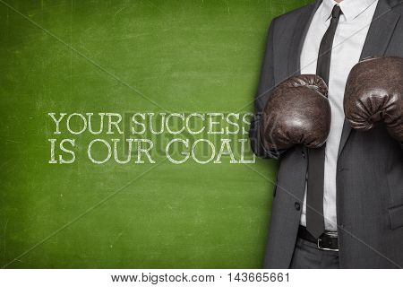 Your success is our goal on blackboard with businessman wearing boxing gloves