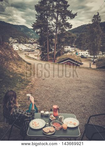 Woman hiker having breakfast in the open air at the campsite, Norway.