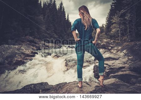 Confident woman posing near waterfall with mountain forest on the background.