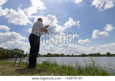 Young man fishing, Fisherman holding rod in action, Angler holding rod in action