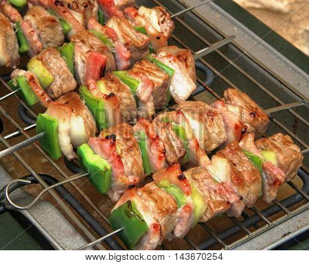 pork skewers on electric bbq grill outside