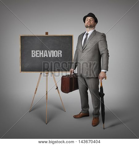 Behavior text on  blackboard with businessman holding umbrella and suitcase