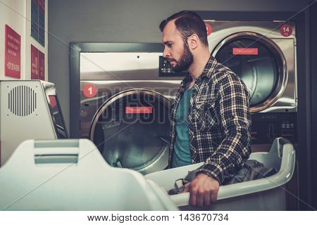 Handsome man doing laundry at laundromat shop