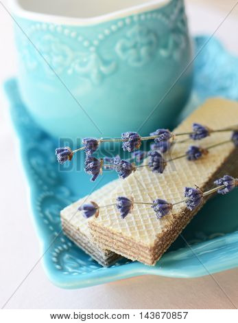 A pair of wafers with lavender flowers and cup of tea on a blue plate