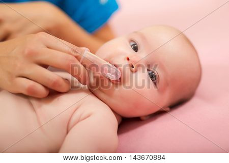 Mother cleaning baby`s mouth with special fingertip brush for children