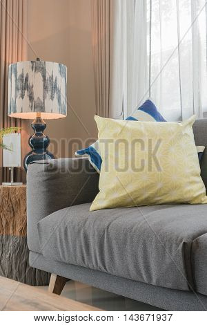 Set Of Pillows On Modern Grey Sofa In Living Room With Lamp