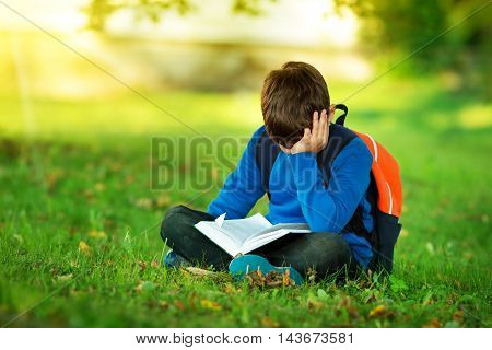 Boy sitting with rucksack in the park and reading a book. Child with a backpack
