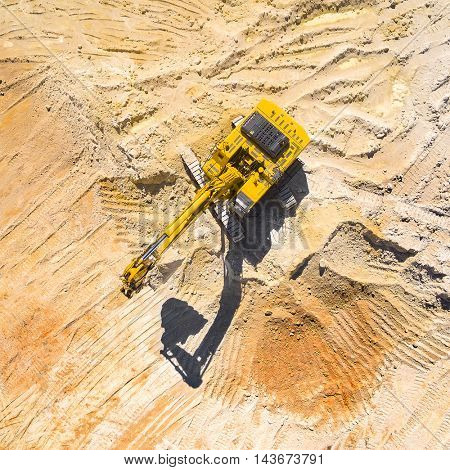 Aerial view of a working excavator in the mine. Industrial background on mining theme. Picture with bold shadow silhouette of vehicle.