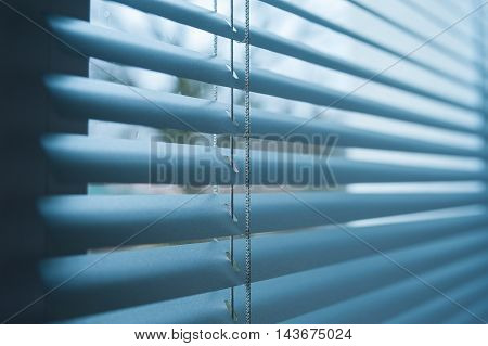 closed plastic blinds on the window with the reflection in the glass
