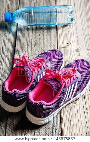 Sport equipment. Purple pink sneakers and water on wooden background