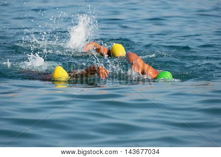 Group of swimmers swim in the sea at the races