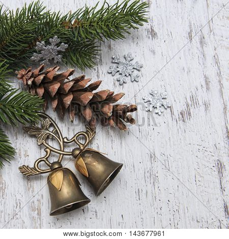 Christmas card with decorations of bells pine and green branches isoalted on textured background
