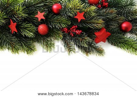 Green branches decoration with red christmas baubles over white