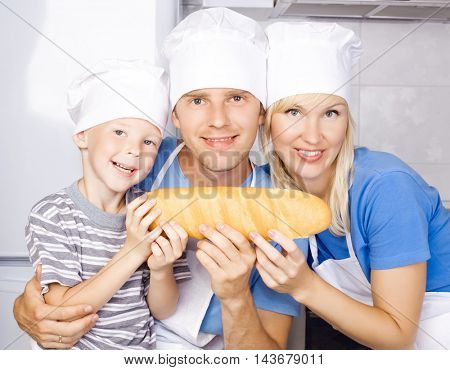 happy family: father, mother and son cooking in the kitchen at home and holding bread