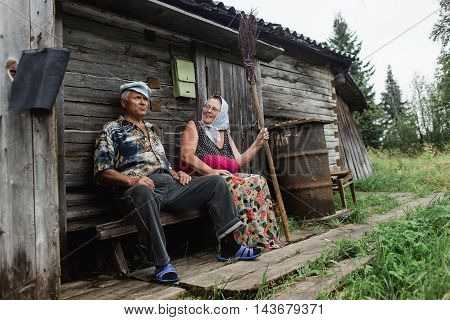 beautiful mature russian couple have fun outside of their house in village. The woman clothed in a scarf keeps the broom.