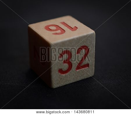 Wooden cube with the number thirty-two on a black background