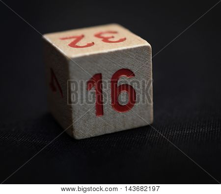 Wooden cube with the number sixteen on black