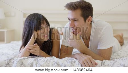 Smiling couple talking while laying down on bed