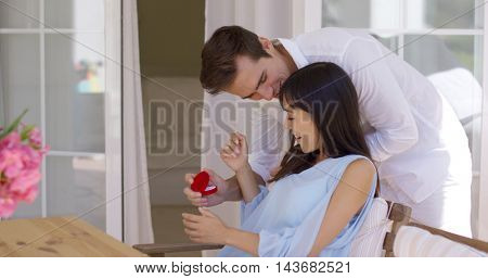 Romantic young man proposing to his girlfriend