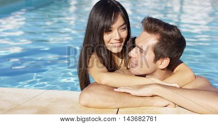 Handsome smiling couple cuddles in swimming pool