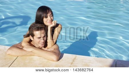 Woman hugs boyfriend and rests elbow on shoulder