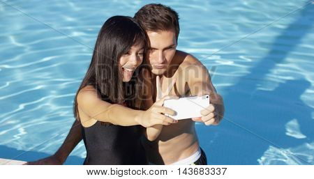 Beautiful woman in black swim suit takes photo