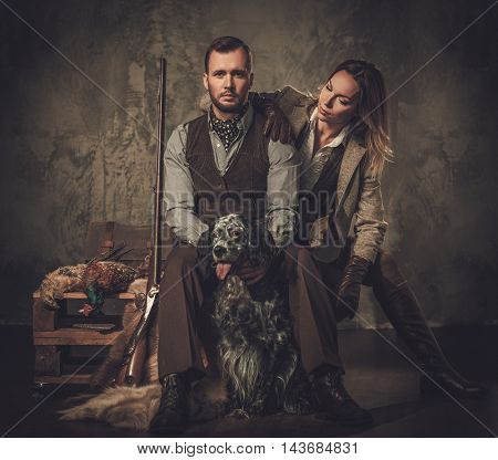 Couple of hunter with a english setter and shotgun in a traditional shooting clothing on a dark background.