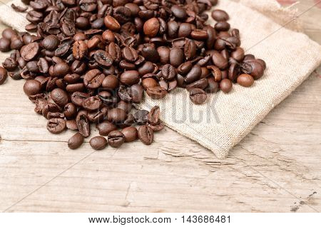 Coffee beans on a rustic wooden background with sackcloth rag