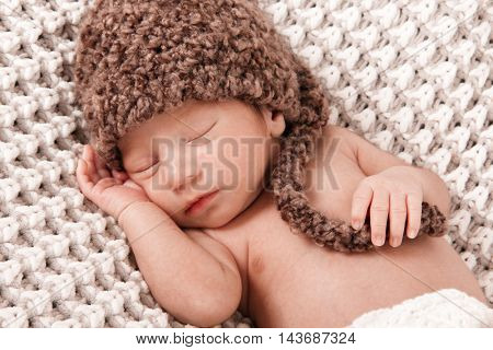 Newborn baby boy asleep on a blanket.