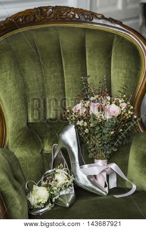 Shoes with a wedding bouquet of flowers on a chair